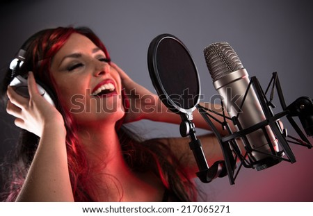 Young singer singing on the studio microphone