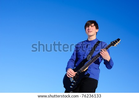 young singer with black guitar isolated on the blue sky
