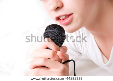 young singer with black microphone in a hand on a white background