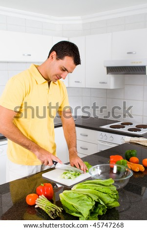 young single man cooking in modern kitchen