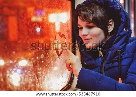 Young single woman in blue jacket sitting in an empty tram and paints on glass heart