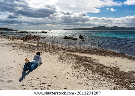 Young single woman looking at awesome cloudy sky lying on the beach sand in autumn or winter season thinking about future destiny. Lonely girl in contact with nature to discover itself Stock foto ©