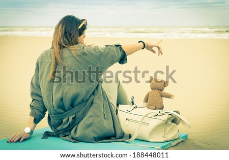 Young single woman sitting at the beach with her teddy bear looking at the sea - Vintage retro nostalgic filtered look