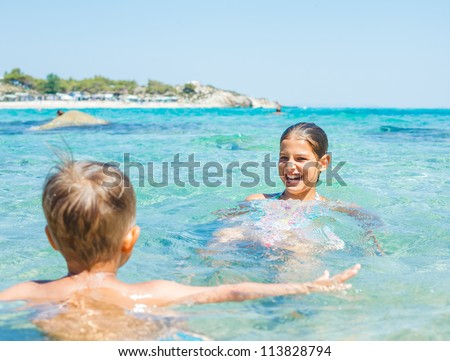 Young sister and brother playing in the transparent sea