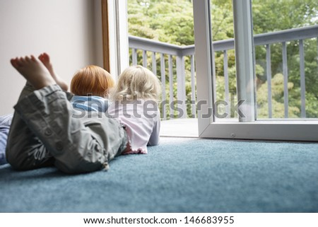 Young sisters looking out through balcony while lying on carpet at home