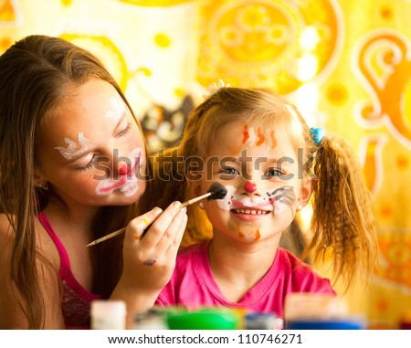 Young sisters playing with painting
