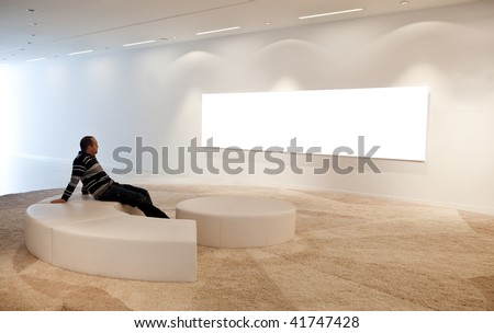 Young sitting man looking at a blank picture on museum wall