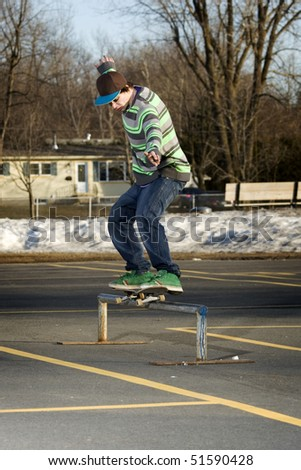 Young skateboarder performing a 50-50 grind on rail