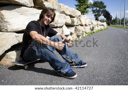 Young skateboarder sitting on board in bike path