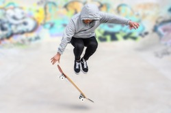 young skater doing jump trick at skate park .