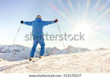 Young skier at the top of mountain raising arms at sky for goal achieved - Sporty man enjoying skiing day with sun light in background - Joyful and successful concept - Warm filter with original flare
