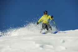 Young skier dressed in bright yellow sportswear riding down the mountain slope in Georgia, Gudauri on sunny day