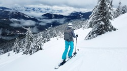 Young skier stands on a gravelly slope with her skis. The mountain slopes are covered with snow. Pine trees covered with snow.