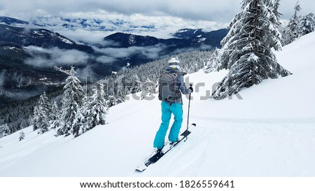 Young skier stands on a gravelly slope with her skis. The mountain slopes are covered with snow. Pine trees covered with snow. Сток-фото ©