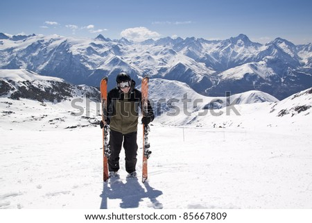 Young skiing man standing in snow mountain landscape with blue sky