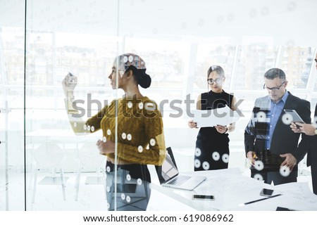 Young skilled afro american elegant dressed female secretary writing on board plan for workshop while professional journalists reading press release of official event in modern conference room
