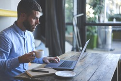 Young skilled male freelancer starting working day early in morning drinking coffee to wake up making new design for website with new advertising content using modern laptop computer and wifi