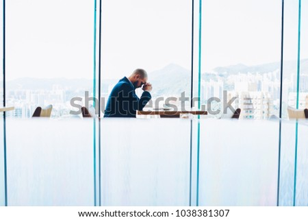 Young skilled trader in formal wear having depression due to failure in financial exchange sitting at wooden table with cup of coffee in modern glass interior. Worried about problems, has lost money