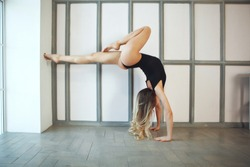 Young skinny woman in black sportwear doing yoga handstand near the window