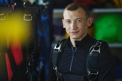 Young skydiver with a parachute is posing surrounded by parachute equipment, portrait.
