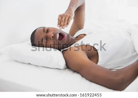 Young sleepy Afro man yawning in bed at home