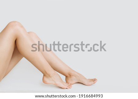 young slender legs of a woman on a white background copy the space. the concept of depilation of the skin Foto stock ©