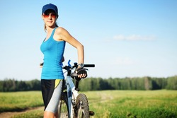 Young slender woman in red glasses standing by bicycle and looking to a camera