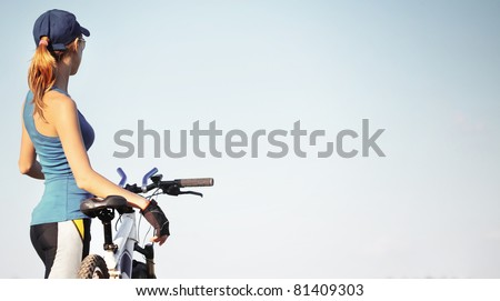 Young slender woman standing by bicycle and looking to a sky. - stock photo