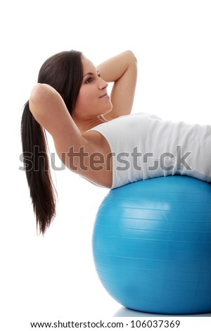 Young, slim and athletic woman doing fitness and exercise with blue ball. Fit girl doing sit-ups and wearing white, sport t-shirt.  Isolated on the white background.