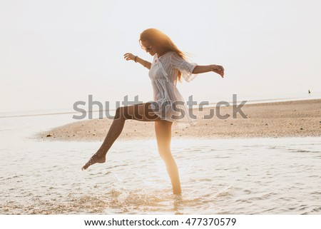 young slim beautiful woman on sunset beach, playful, dancing, running, bohemian outfit, indie style, summer vacation, sunny, having fun, positive mood, romantic, splashing water, silhouette, happy