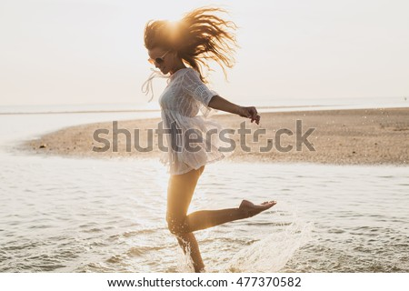 young slim beautiful woman on sunset beach, playful, dancing, running, bohemian outfit, indie style, summer vacation, sunny, having fun, positive mood, romantic, splashing water, silhouette, happy #477370582