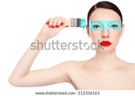 Young slim beautiful woman with painting brush and paint on her face, over white background