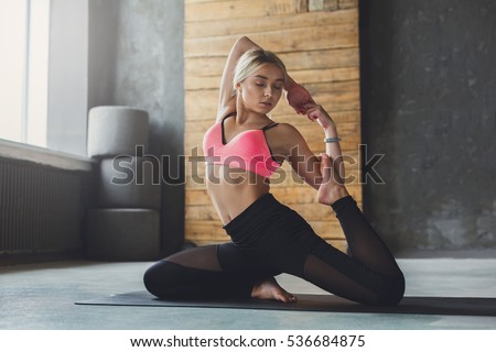Stock Photo Young slim blond woman in yoga class making beautiful asana exercises. Girl do mermaid pose, variation of rajakapotasana. Healthy lifestyle in fitness club. Stretching