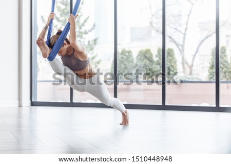 Young slim girl fitness model doing stretching using hanging bindings in gym with large windows. Variation of monkey god pose, splits, hanumanasana. Concept of healthy lifestyle. Anti-gravity yoga