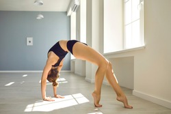 Young slim girl gymnast standing in bridge position and practicing rhythmic gymnastics or pilates in light spacious studio with sunlight. Professional gymnast during workout