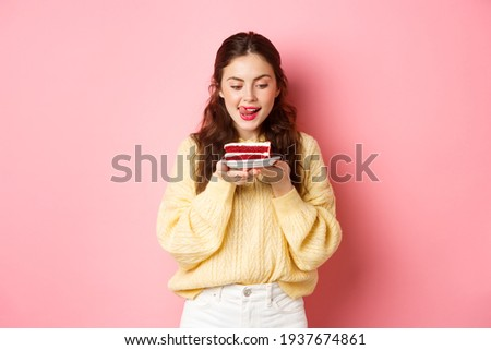 Young slim girl lick her lips from temptation, looking at delicious piece of cake with yearning to bite it, standing with dessert against pink background Stock photo ©