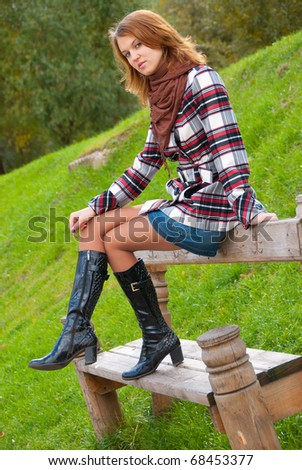 Young slim girl sitting on a park bench