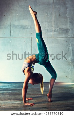 Young slim gymnast woman in sports clothing standing upside down on wall background.