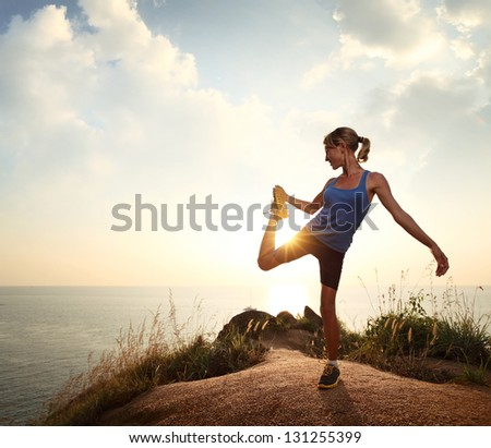 Young slim lady doing stretching exercises on a rural path with grass and cloudy sky on the background