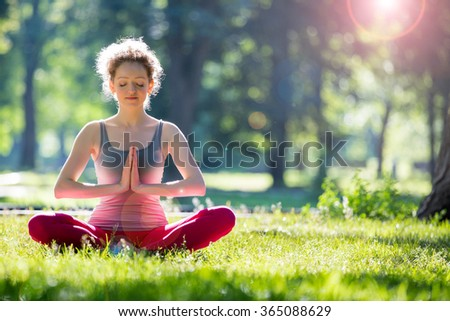 Young slim lady training in the park. Doing yoga exercises on fresh air and enjoying early morning. Healthy lifestyle
