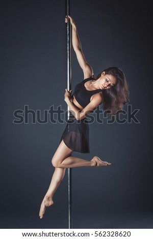 Young slim pole dance girl of asian appearance on a black studio background Сток-фото ©