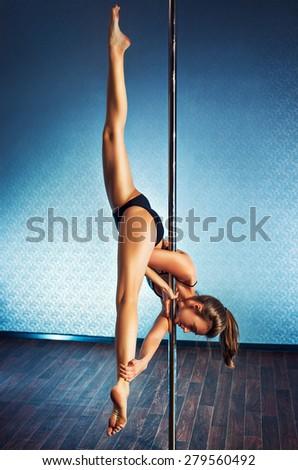 Young slim pole dance woman making splits upside down.