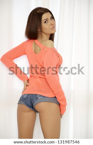 Young slim sexy and attractive brunette woman in orange sweater and blue jeans short against the window