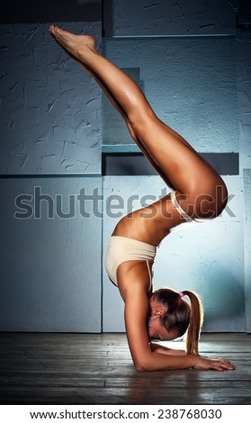 Young slim sexy gymnast woman in lingerie standing upside down on stone wall background.