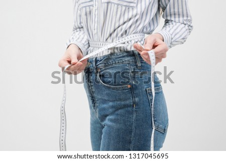 Young slim slim girl measures the waist tape in jeans and shirt on a white background. Concept of dieting. #1317045695