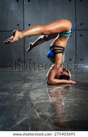 Young slim sports woman standing upside down on stone wall background.