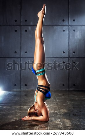 Young slim sports woman standing upside down on wall background.