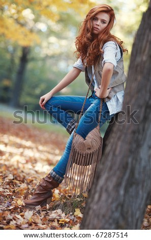Young slim woman autumn portrait. Camera angle view.