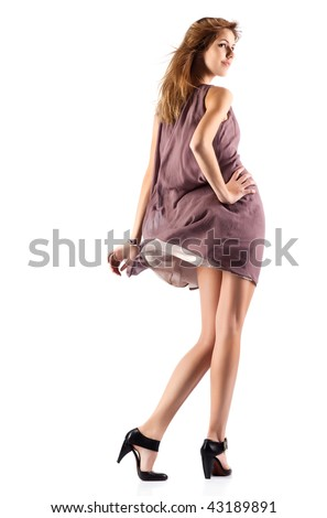 Young slim woman in fluttering dress. Isolated on white. - stock photo