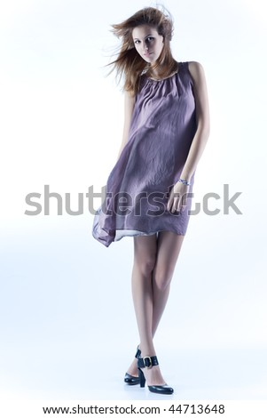 Young slim woman in fluttering dress. Soft blue tint.